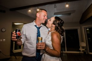 bride and groom singing to each other at wedding reception with coke and san Pellegrino