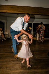 groom dancing with flower girl at wedding