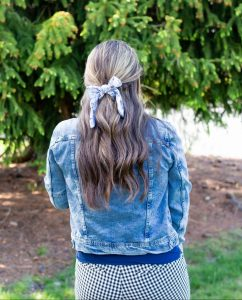 balayage hair halfup hair style with hair scarf on woman wearing denim jacket and gingham shorts