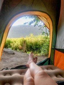 Woman's legs in tent with a view of the forest and hills