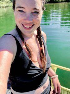 Woman in black bikini smiling while on boat on lake