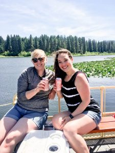 Two women drinking wine on boat on lake