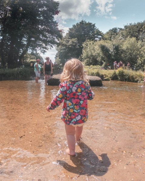Image of a toddler paddling in a river in Norwich