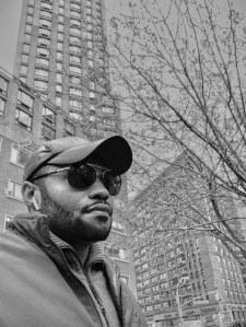 Apple Airpods Gstar sweater and Lab Series products Winter weather during Spring in NYC Tyrone Smith in Union Square Park wearing Barneys jacket Louis Vuitton Shades