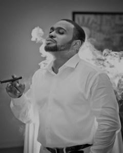 Cigar Aficionado Celebrity Influencer famous muisc producer Tyrone Smith enjoys hand rolled cigars in Montego Bay Jamaica Secrets St James Resort