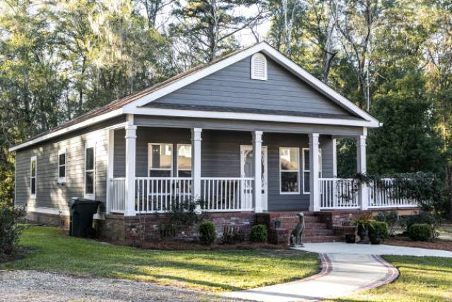 Small blue gray mobile home with a front and side porch. It has a white porch railing out in the country on land shared by a larger siding house.