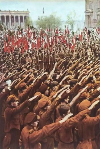 Gęste szeregi członków Hitlerjugend wznoszących prawe ramię w geście Heil Hitler.