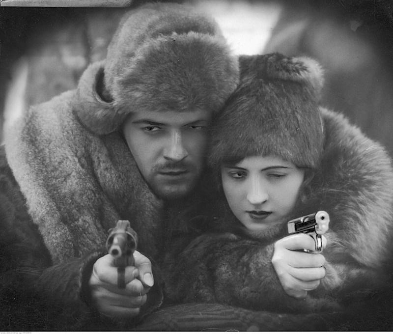 Adam Bronisz i Jadwiga Smosarska w ciepłych futrzanych czapkach i korzuchach, stojący lub siedzący twarzą przy twarzy. Oboje trzymają pistolety i mierzą do celu.