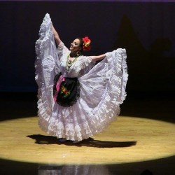 Maria Patiño dons a white dress for the state of Veracruz, Mexico during a performance (photo courtesy Maria Patiño).