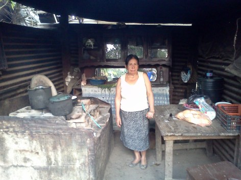"""Carmen, pictured here in her """"open"""" kitchen, works 12 hours a day to support herself and her son's family of 6 who occasionally is able to find work.  The team will be repairing part of their roofing as well as adding a wall and door to her kitchen."""