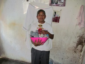 """Hamilton was the only one home when we visited because he was on break from school for Holy Week.  His sister Fabiola was on her way home from work to get ready to go to school.  Both of the kids are able to go to school now thanks to sponsors through the Serving At Risk Families Ministry!!  I told him to make sure he didn't eat all the candy before the rest of his family got some and he laughed and said """"maybe"""" :)"""