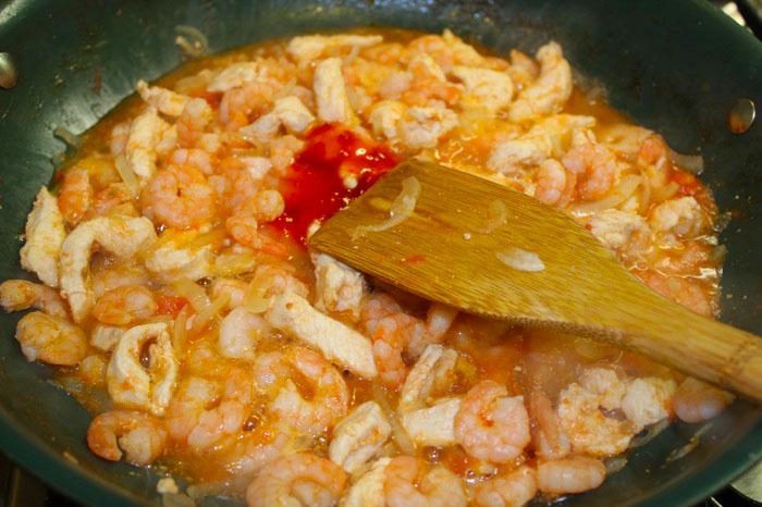 После того как помидоры превратятся в пюре, а лук станет мягким и прозрачным добавить соус чили или красный перец