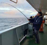 "PhD Student Andreas Rogge fishing while the ship is stationary during an MSS cast. When asked what he hoped to catch, he replied, ""Anything!"""