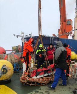 A pulka sledge being loaded on to the basket with bear guards Oceanographer Vladimir Bogdanov and Hydrologist Vasily Kuznetsov looking on.