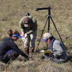 Breen (left) teaches her students about vegetation sampling in the field, using an optical device on a tripod to measure plant cover at each point along the transect. (Photo by H. Cheong)