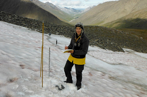 Tedesche uses a depth probe to measure the depth of softer top layers of snow and an ice auger to measure the depth of harder, older layers of snow, firn, and ice in the central Brooks Range, Northern Alaska. (Photo by C. Ciancibelli)