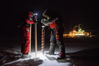 Drilling holes in ice during MOSAiC. Photo by Esther Horvath.