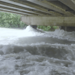 Water rushes under a Juneau bridge during a flood.