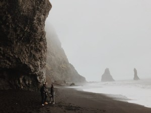three people standing near seashore viewing cliff covered with fogs
