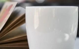 Benefícios do café. Imagem contém uma xícara branca com um livro em segundo plano.