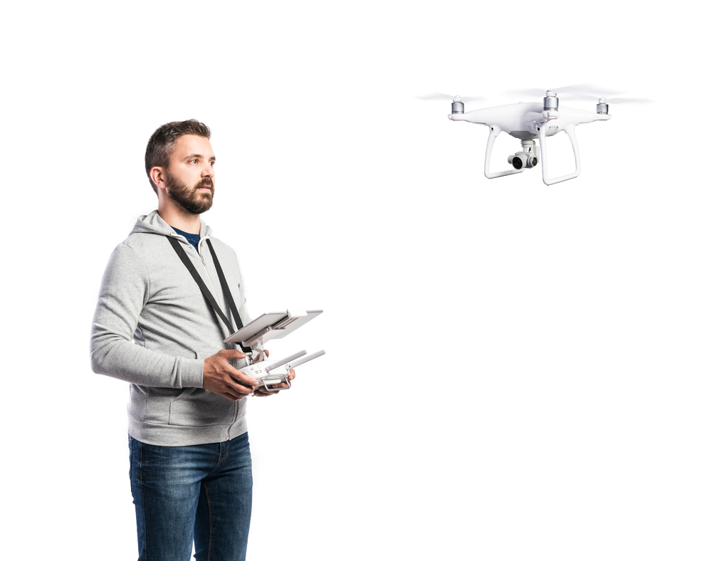 Man flying a drone holding a control transmitter