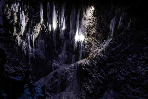 Image nocturne d'un grimpeur dans la cascade de glace Glasnost en Maurienne