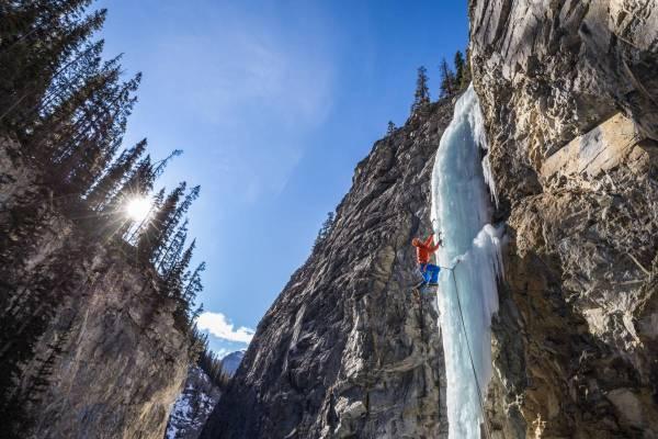 Un grimpeur gravit une colonne de glace illuminée par le soleil canadien, Alberta