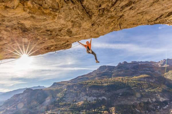 Un grimpeur pendu à ses piolets se balance les pieds dans le vide sous un imposant toit dans le Queyras près de Briançon