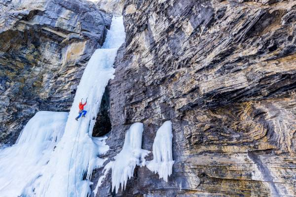 Vue graphique du bas de la cascade de glace The fang and the fist enchassée dans une paroi ocre, Ghost Valley, Alberta