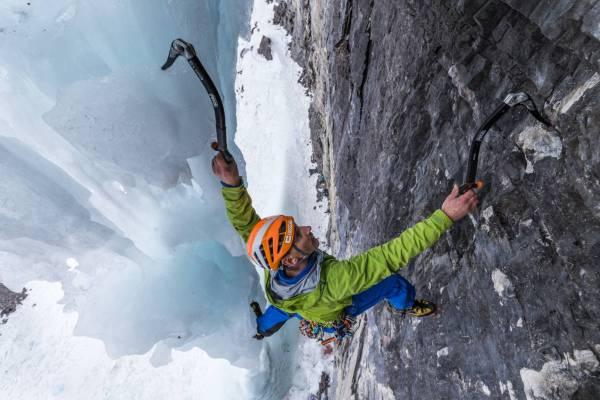 Vue plongeante d'un alpiniste entre roche et glace dans la voie The real Big Drip, Ghost Valley, Alberta