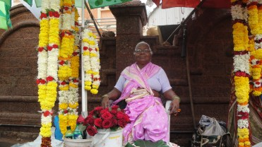 A lady selling garlands outside a temple