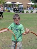 Sword-fighting boy figures out how to hoop one hoop on each hand.