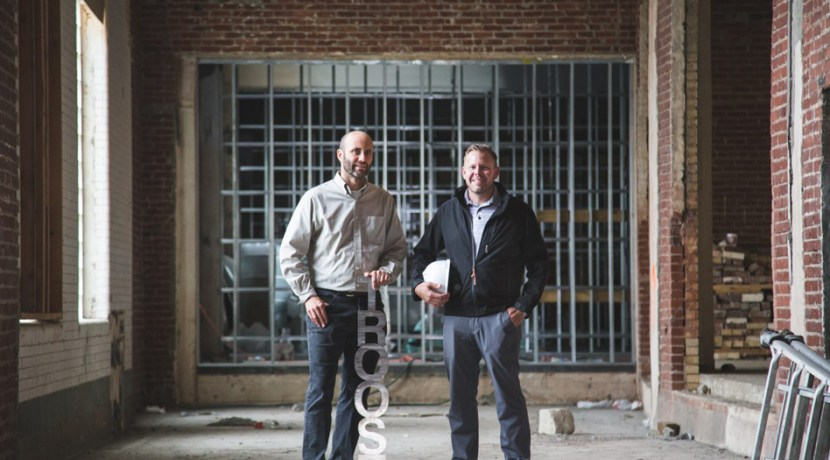 Two men standing in undeveloped building holding a metal sign reading Troost
