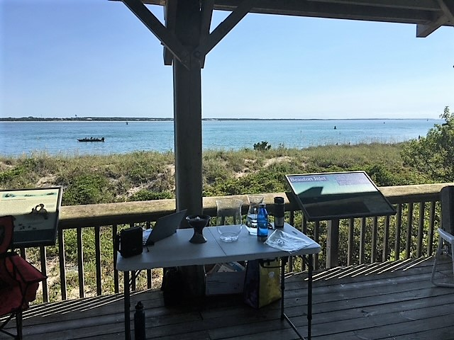View of the table with service elements in front of the dunes and the ocean