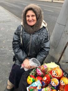 Old Russian lady Babushka selling Matryoshka dolls in Moscow