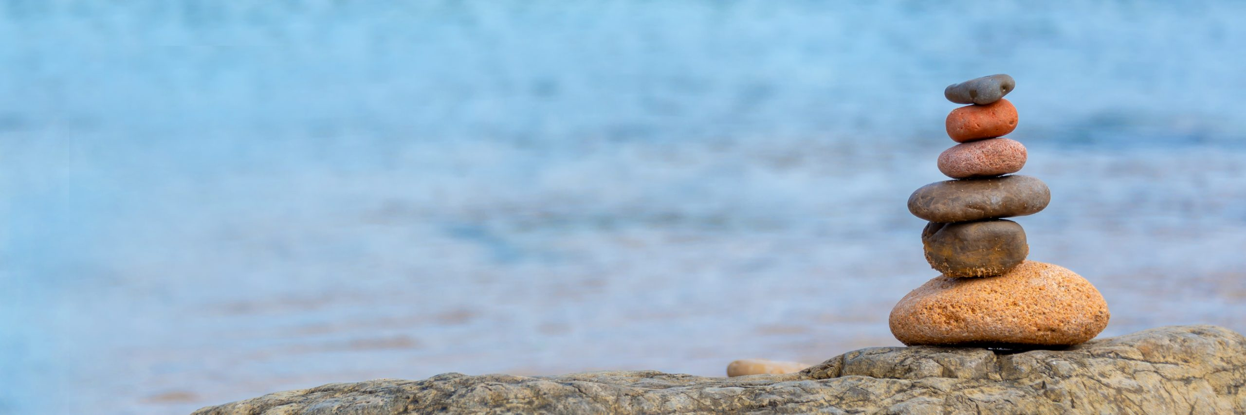 Pile of pebbles on a beach, panoramic blue water background