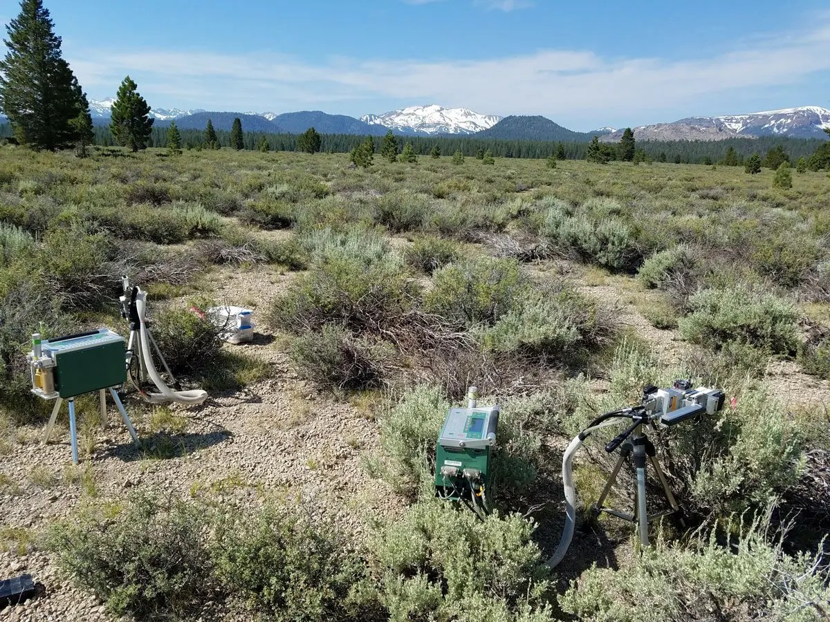 Several pieces of scientific equipment in a field of sagebrush in eastern California against a backdrop of snowy mountain peaks.