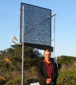 Dan Fernandez, chair of Science and Environmental Policy at CSU Monterey Bay, stands by a fog collector at Fort Ord Natural Reserve. His collectors meet international specifications, right down to the mesh. Fernandez bought 800 square meters of the official mesh from the manufacturer while attending a conference in Chile, making a special taxi trip on his way to the airport. Photo courtesy of Dan Fernandez.