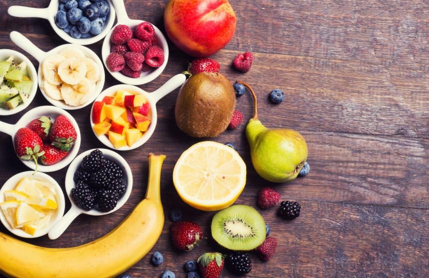 Berries (strawberry , raspberry , blueberries , blackberries ) & fruits ( banana , kiwi , peach , lemon ) in bowl