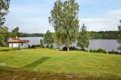 Gräsmattan framför stora huset ner mot sjön