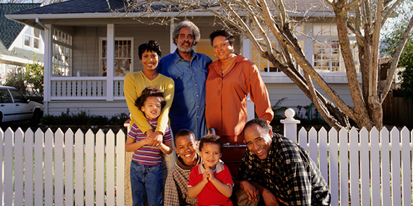Multi generational family standing at gate in front of a home