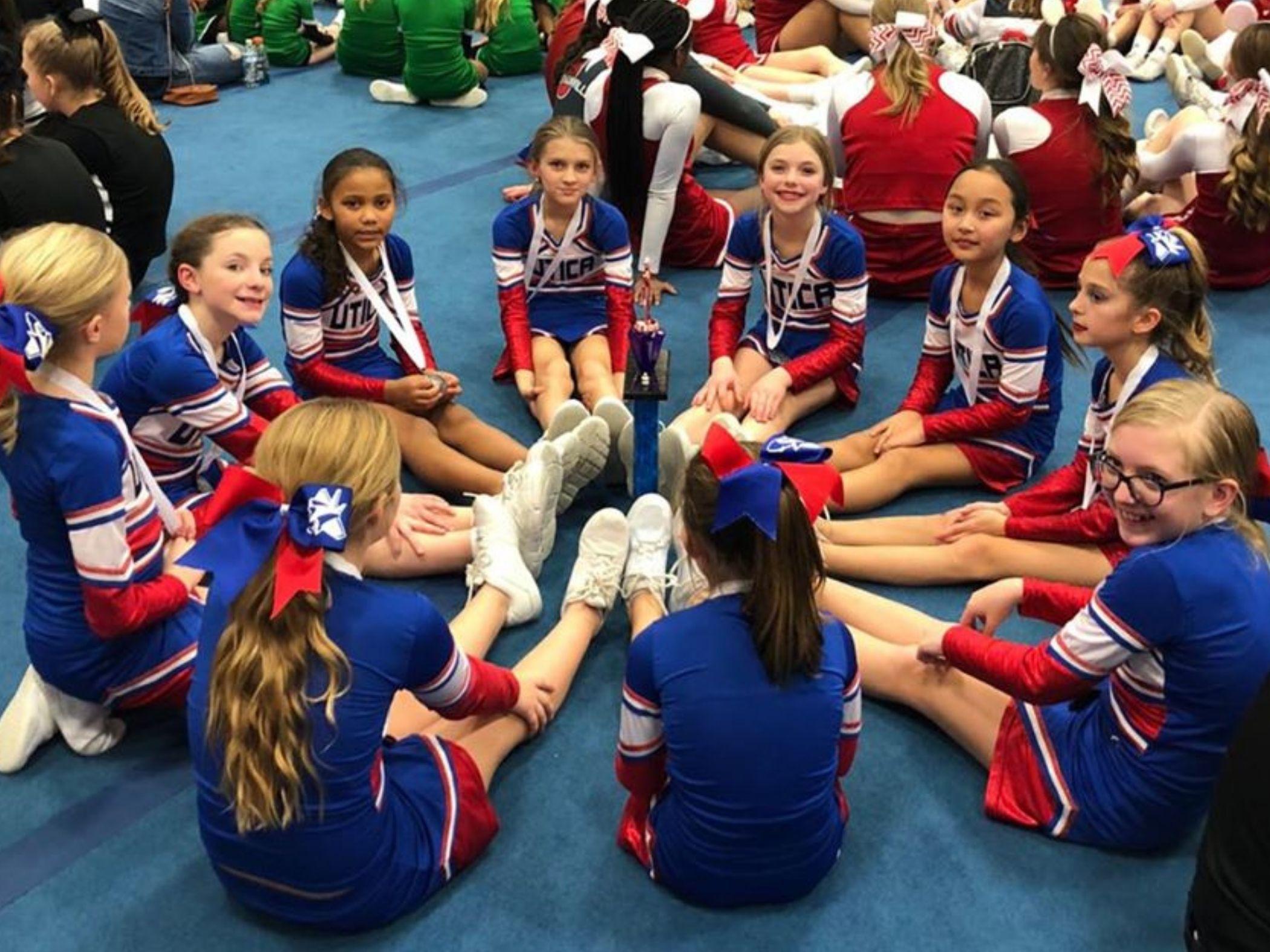 Cheerleaders sit in circle around trophy