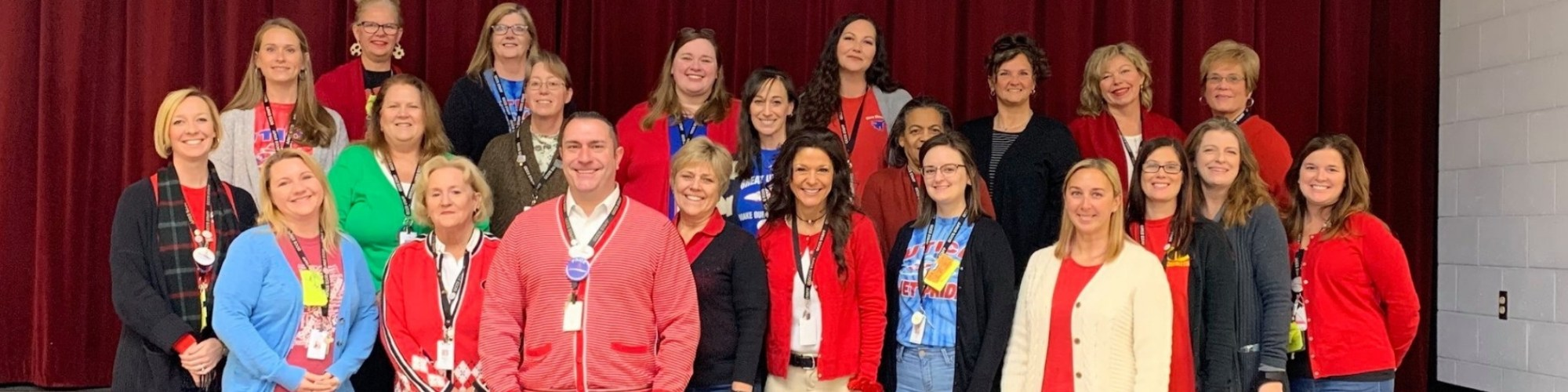Teachers pose together on stage