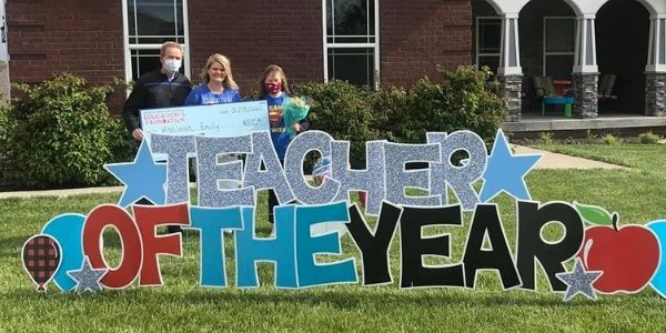 Teacher poses with flowers after winning Teacher of the Year