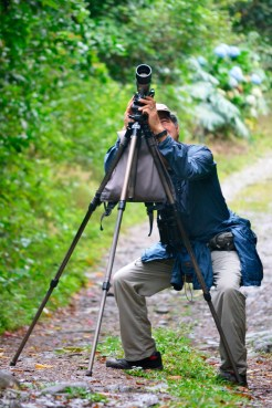 Russ Kumai focuses his scope on a spotted bird.