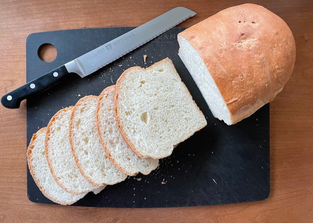 a loaf of bread with five slices and a breadknife on a black cutting board