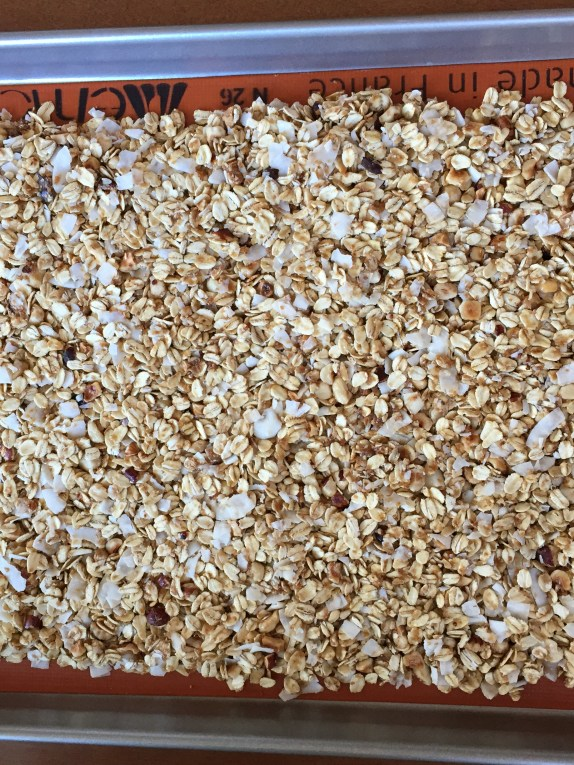a baking sheet and silicone mat covered in unbaked granola