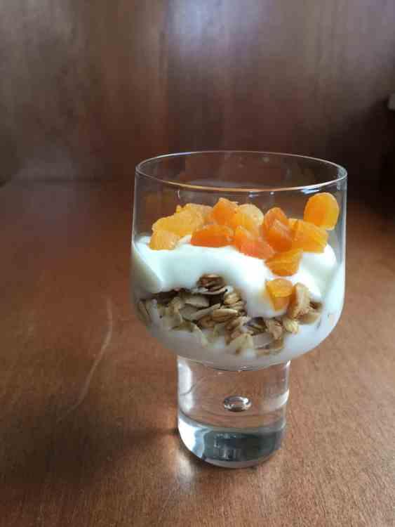 a parfait glass filled with granola, yogurt, and chopped dried apricot