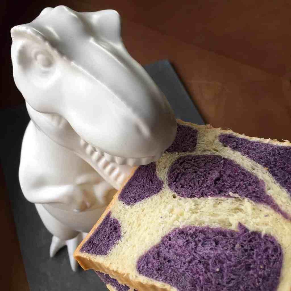 a dinosaur cookie jar eating a slice of purple cow milk bread