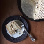 a slice of tiramisu cake on a plate next to the cake